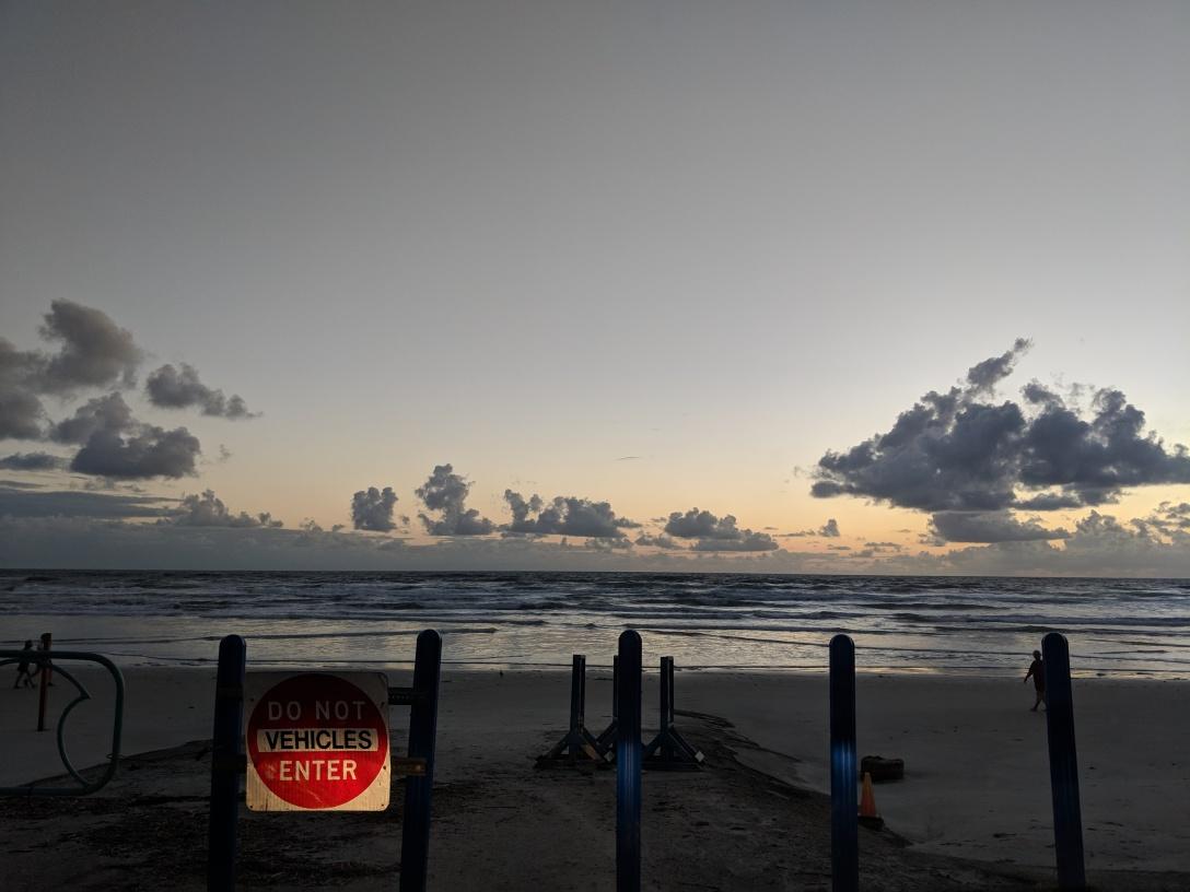 "east coast beach scene sunrise, wood poles and bottom half a ""do not enter"" sign"